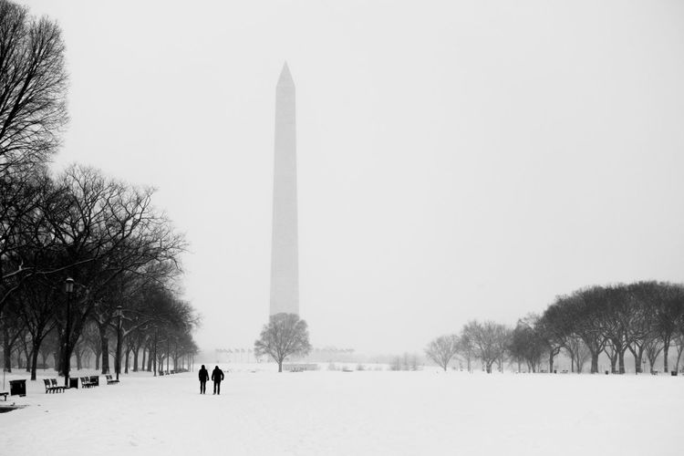 Snowcapped Field Against Washington Monument In Foggy Weather