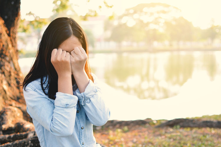 Woman Covering Face With Fists By Lake