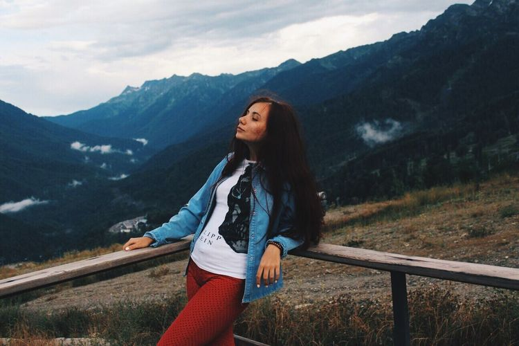 Full length of young woman on mountain against sky