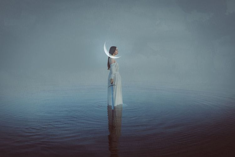 Digital Composite Image Of Woman Holding Sward While Standing In Sea Against Sky