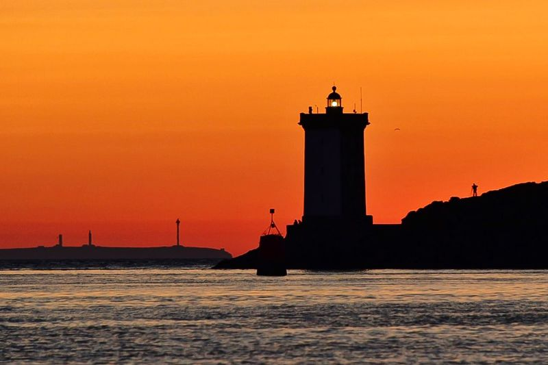 Silhouette lighthouse at sea against sky during sunset