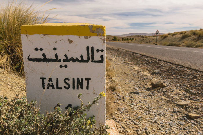 A kilometer stone with Arabic characters on it saying Talsint, Morocco. Africa Arabic Arid Climate Calligraphy Desert Direction Distance Distant Indicator Kilometer Letter Milestone Morocco Road Roadside Route Sign Stone Talsint Travel White