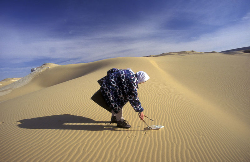 Side view of man picking up plastic bottle on desert
