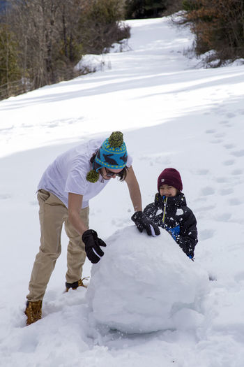 A young guy in a T-shirt and a cap makes a snowman with his younger brother in the winter forest on a nice sunny day. Snow Cold Temperature Winter Leisure Activity Lifestyles Nature Warm Clothing Real People Full Length Two People Child Day Clothing Males  Mountain Men People Outdoors Teenager Snowman Fun Winter Time Brothers Snowy Making