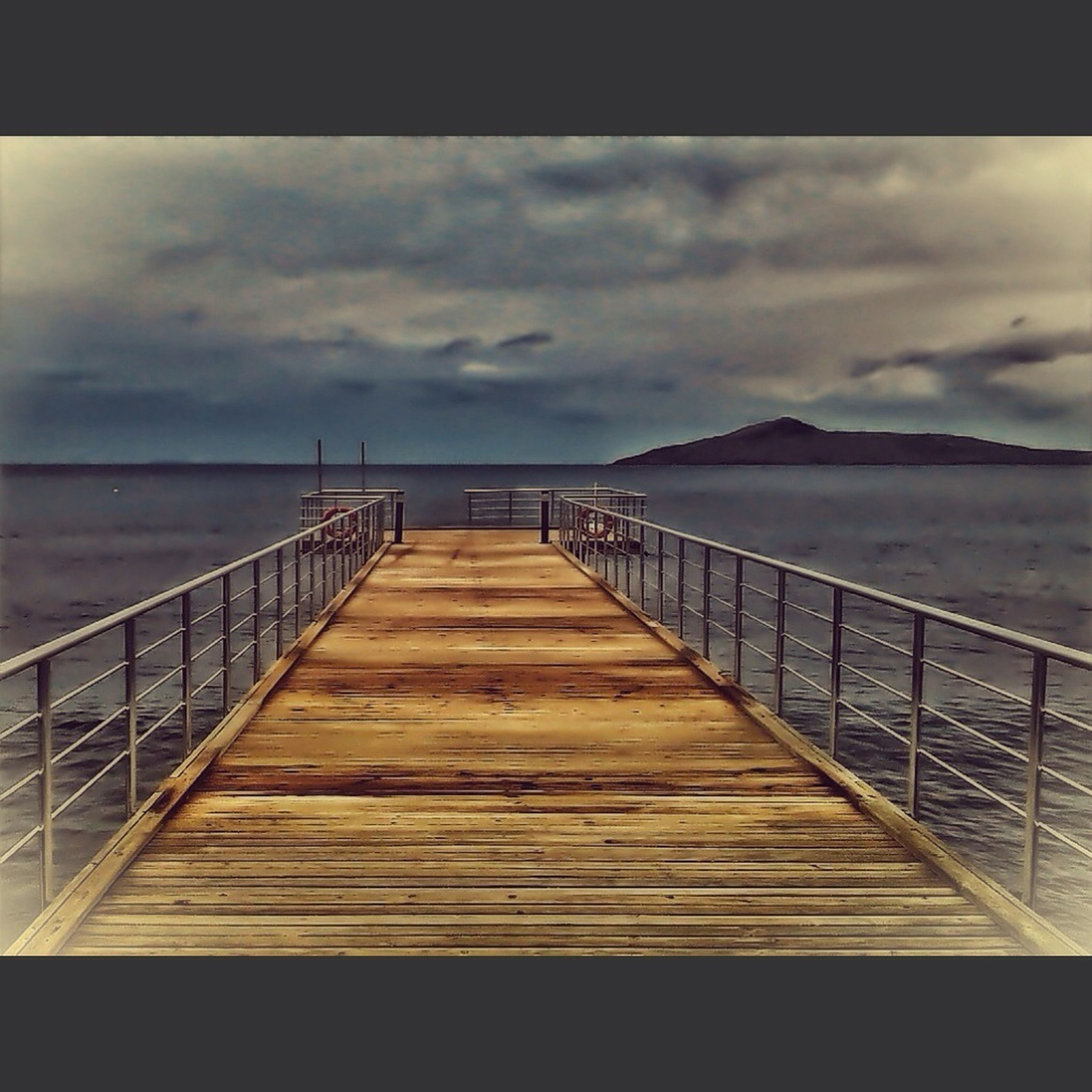 sea, water, sky, pier, railing, tranquil scene, wood - material, cloud - sky, tranquility, scenics, horizon over water, beauty in nature, nature, jetty, cloud, the way forward, cloudy, boardwalk, wood, idyllic