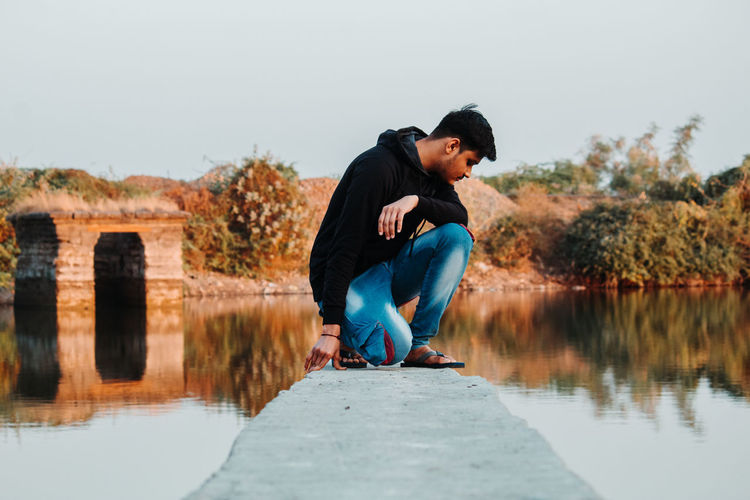 Man kneeling on concrete over lake against clear sky