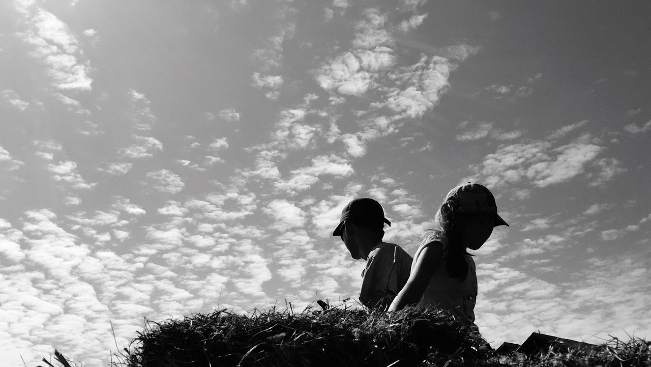 Low Angle View Of Friends Sitting On Hill Against Sky