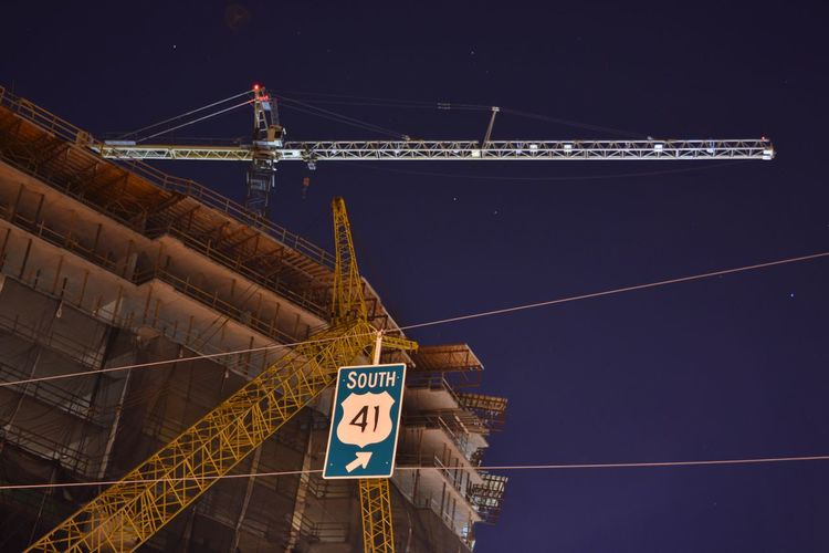 Low angle view of cranes by incomplete building against sky at night