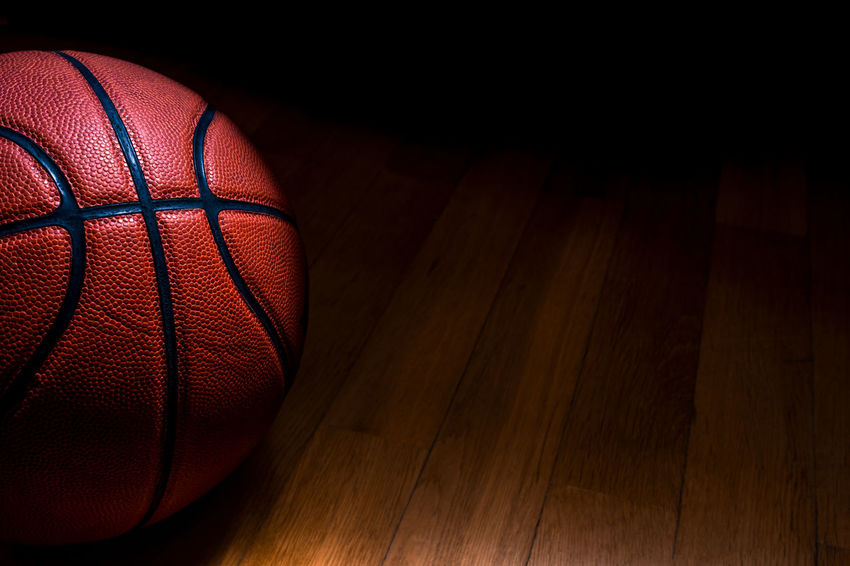 Arts Culture And Entertainment Ball Basketball - Sport Close-up Competition Competitive Sport Copy Space Dark Hardwood Floor Indoors  Leather Leisure Activity Light - Natural Phenomenon No People Orange Color Pattern Recreational Pursuit Shadow Single Object Sphere Sport Sports Equipment Team Sport Textured  Wood - Material