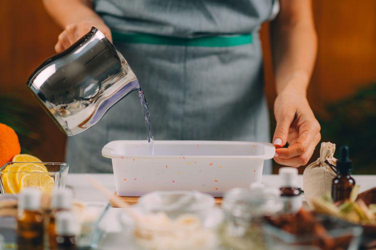 Pouring purple liquid homemade soap mass into silicone mold.
