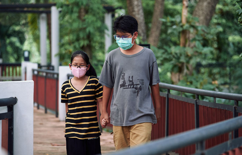 Brother and sister walking together in a public park during the covid-19 pandemic