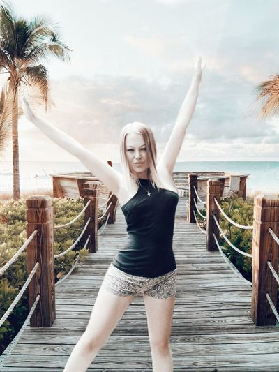 Portrait Of Young Woman With Arms Raised Standing On Pier At Beach