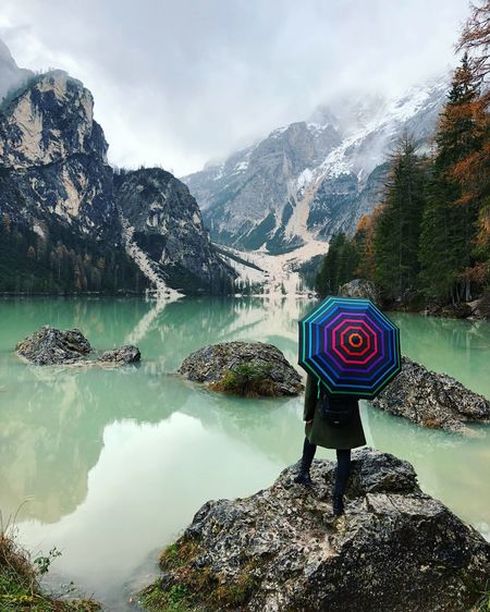 Rear View On Woman Standing With Umbrella On Rock In Lake Against Mountains