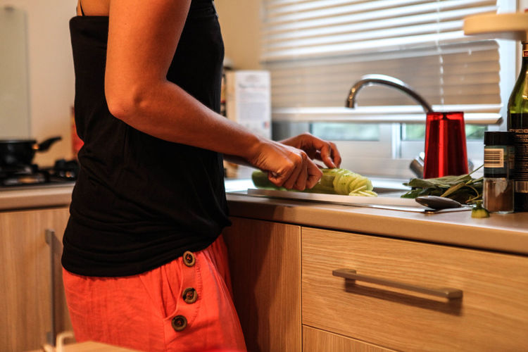 Midsection of woman holding hands at home