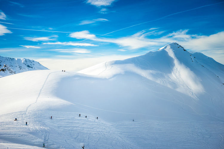 Two snowboarders climbing the snowy peaks for off peak boarding in the powder
