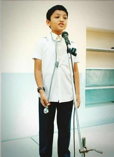 Boy in doctors costume talking on microphone