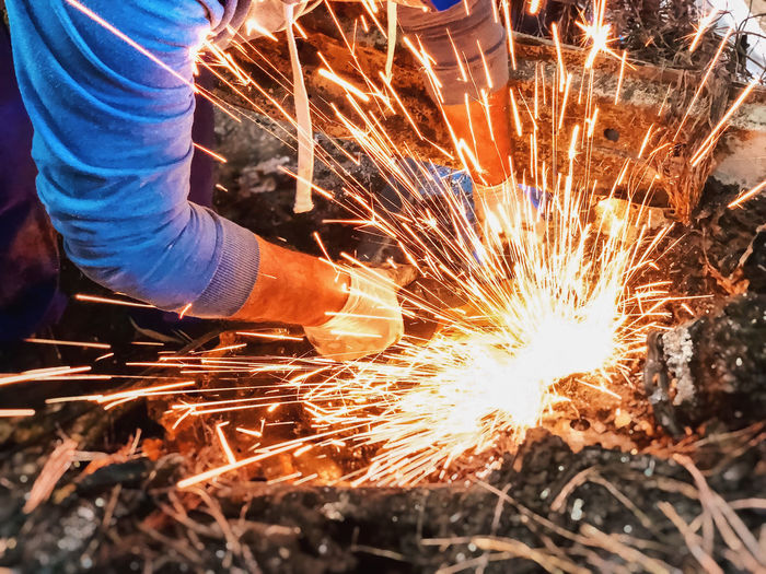 Low angle view of man working on metal