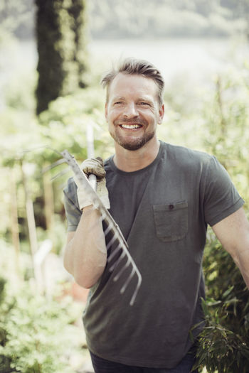 Portrait of smiling man holding plant