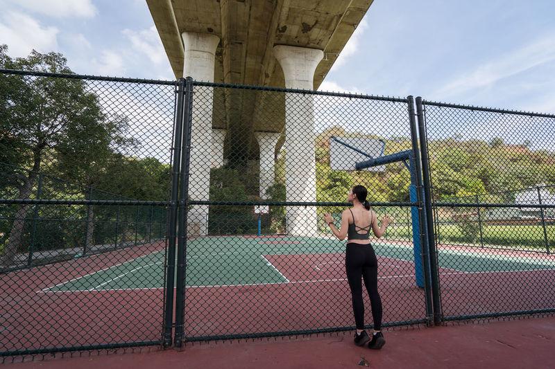 Full length of woman on chainlink fence against bridge