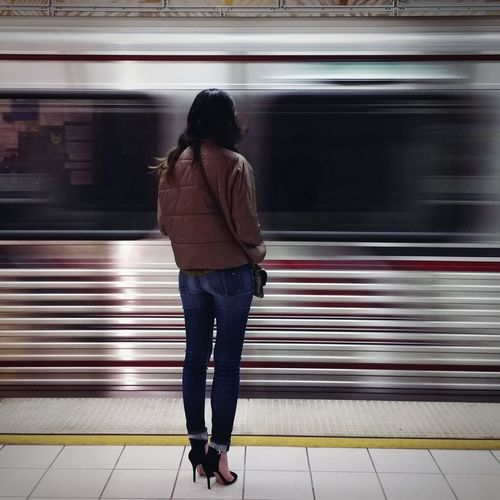 Full length rear view of woman standing on railroad station platform against blur train