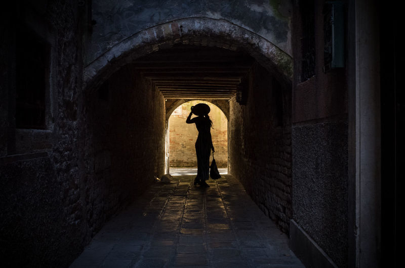 Silhouette woman standing in arch pathway