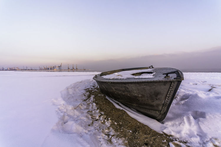 Snow covered boat on shore against sky during winter