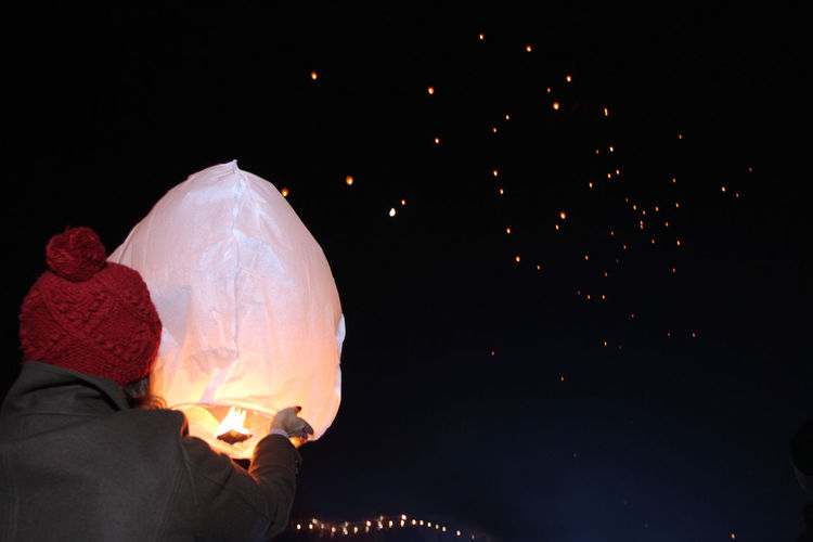 Rear view of woman holding illuminated paper lantern against sky at night