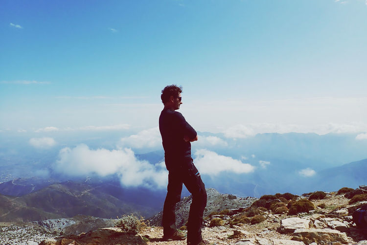 Man standing on rock looking at mountain against sky
