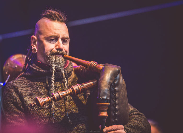Mature Man Playing Bagpipes On Stage