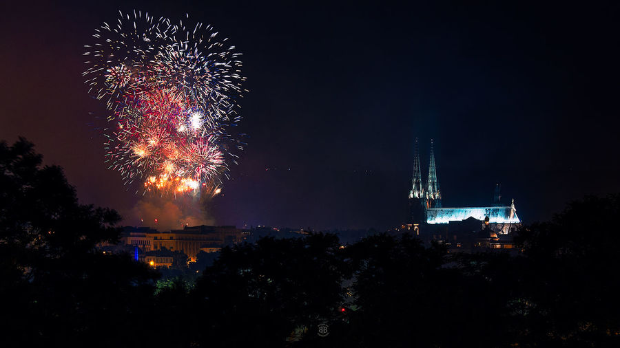 Illuminated fireworks by historic cathedral against sky at night