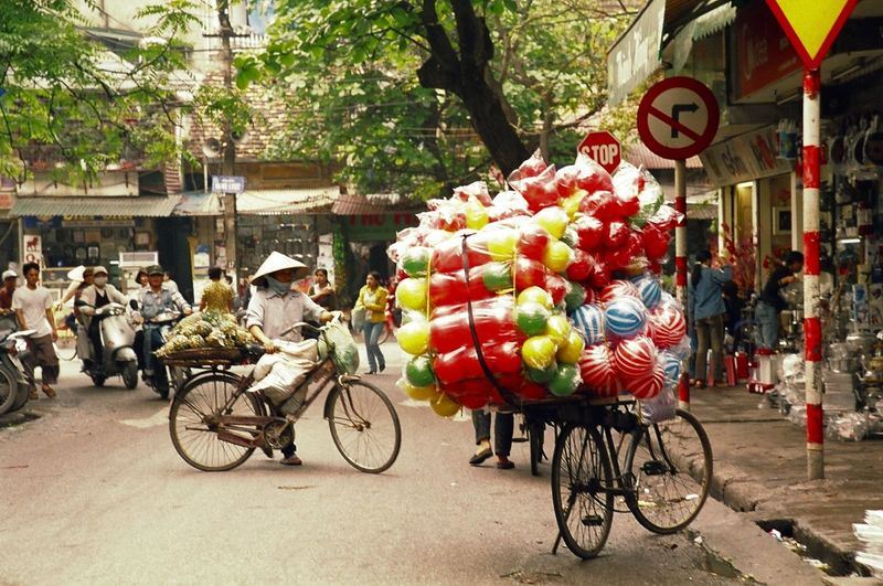 Street Vendors Selling Various Objects On Bicycle