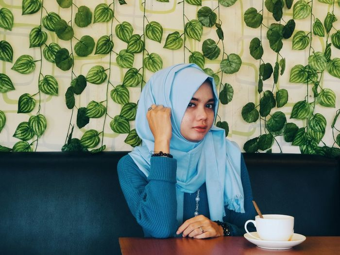 Portrait of young woman wearing hijab while sitting at table in restaurant
