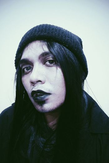 Close-up portrait of genderblend young man wearing lipstick against wall