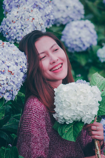 Portrait of a beautiful young woman holding flower bouquet