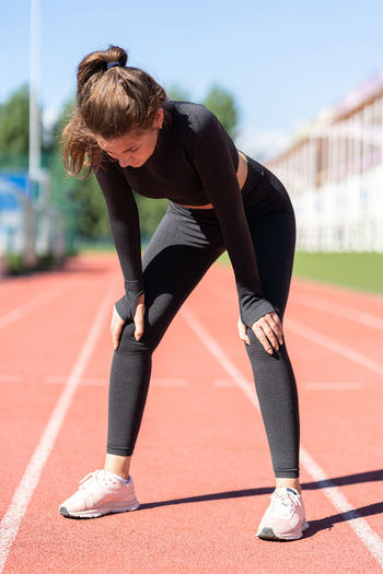 Full length of tired woman standing on running track
