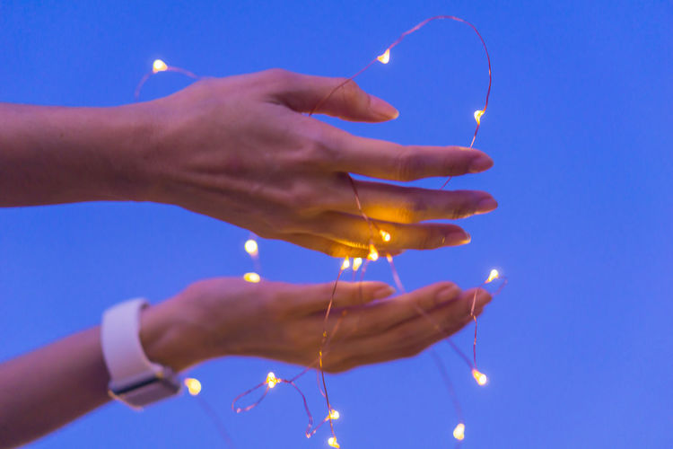 Close-up of hand holding lit candle against sky