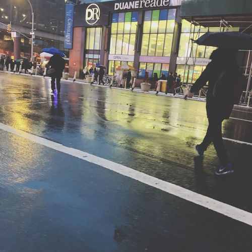 People walking on wet road in city during rainy season