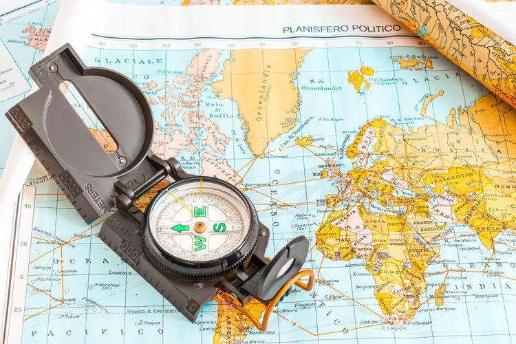 High angle view of navigational compass on world map