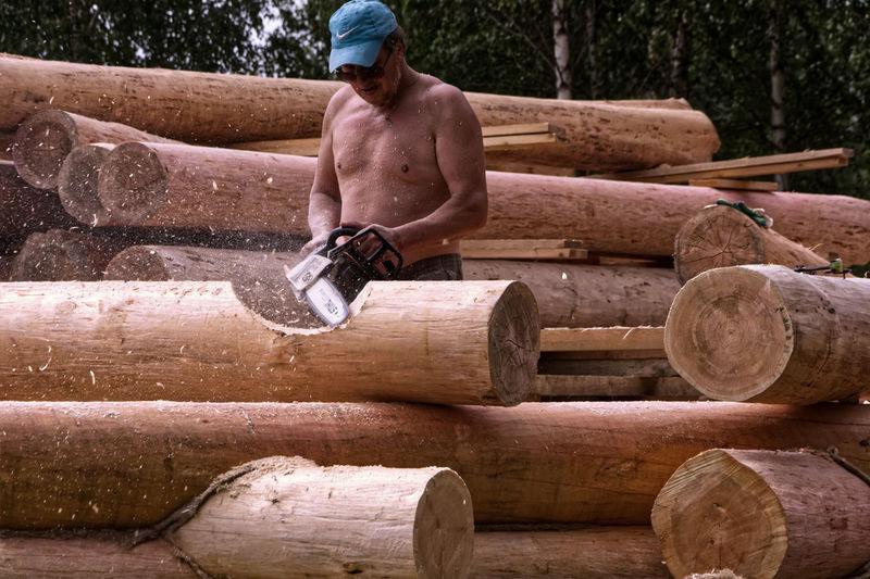Full length of shirtless man on log in forest