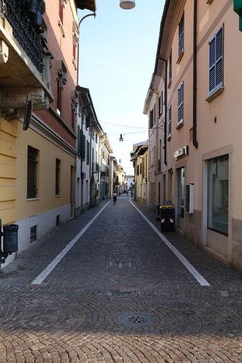 Empty road along buildings
