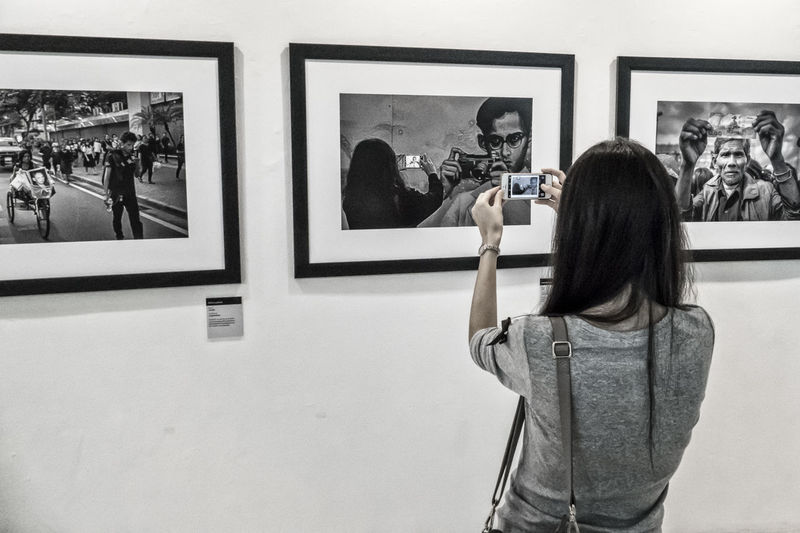 Photographing the photographer. A woman taking a photo of a picture of a woman taking a photo of the past king of thailand with is camera. BACC Bangkkok Bangkok Art Cultural Center Exhibition Indoors  KING BHUMIBOL Mirrored Museum Photograph Picture Frame Royal Mourning Thailand