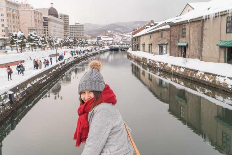 Woman by canal in city during winter