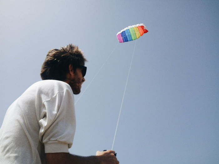 One Person Sky Leisure Activity Clear Sky Young Adult Lifestyles Day Kite - Toy Copy Space Low Angle View Flying Side View Nature Paragliding Men Holding Young Men Real People Sport Wind