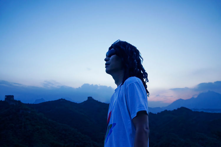 Side view of man looking away against sky during sunset