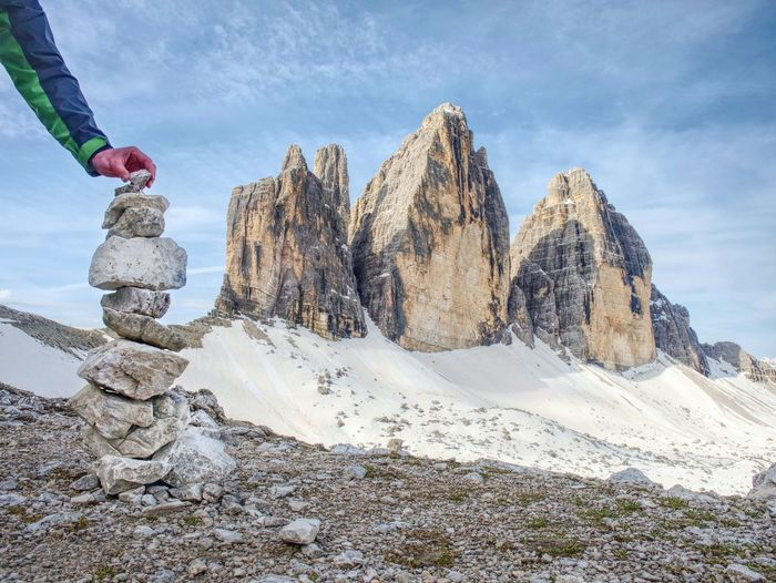 Hiker hand building stony pyramid bellow the three peaks of lavaredo. spring hike in italy alps.