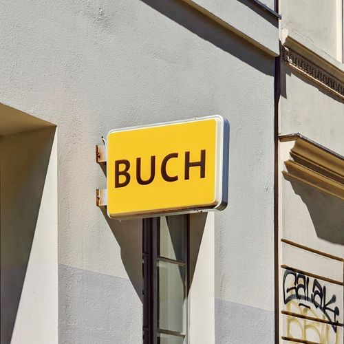 Close-up of yellow sign on wall