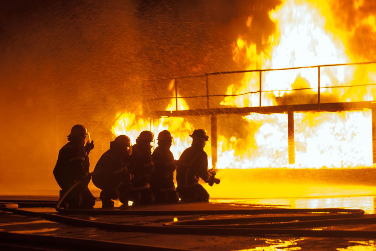 Silhouette Firefighters Spraying Water On Fire At Night