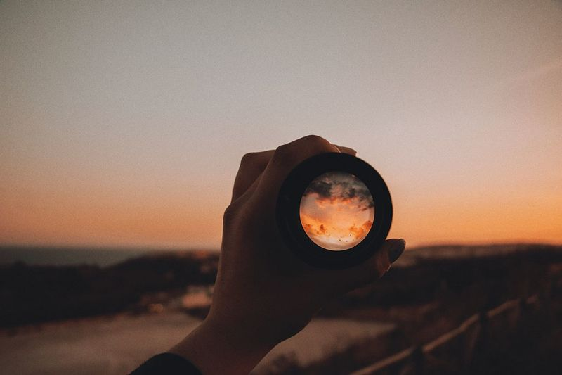 Close-up of woman hand holding lens against clear sky during sunset