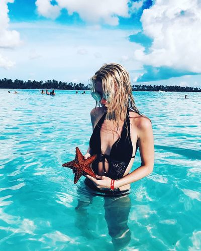 Young Woman Holding Starfish While Standing In Sea Against Sky