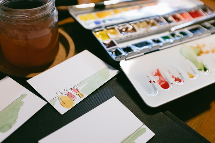 Painting Sketching Business Card Table Indoors  Still Life Close-up High Angle View No People Paper Focus On Foreground Selective Focus Art And Craft Business Container Choice Food And Drink Plate Variation Finance Multi Colored Bill Restaurant Creativity